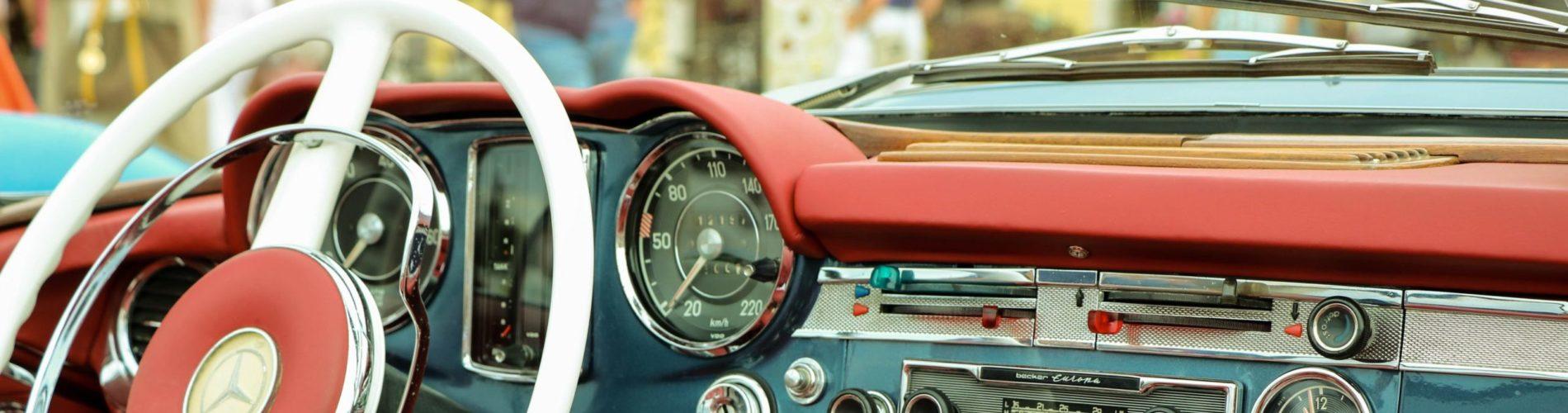 A photo of an older car steering wheel/dash