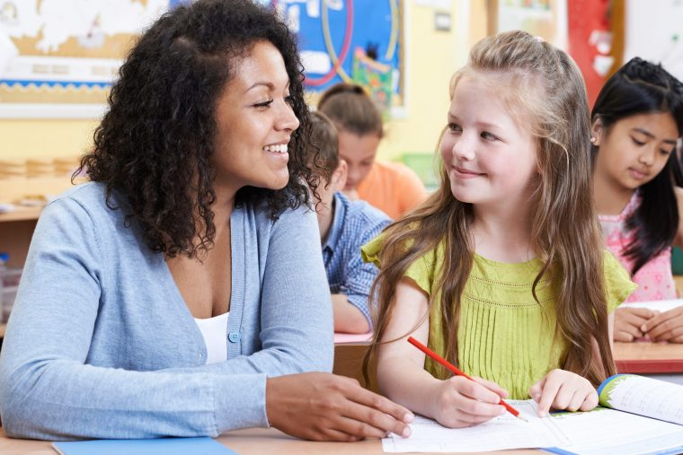 Teacher With Female Elementary School Pupil In Class