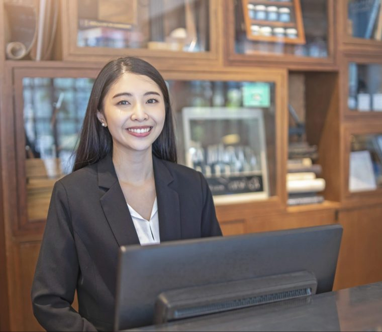 Receptionist standing behind a marble counter in front of a computer monitor smiling.