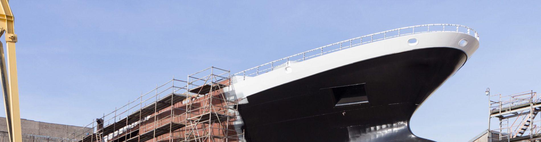Hull of ship under construction at shipyard.