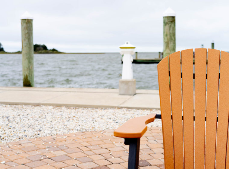 A photo of an Adirondack chair with a body of water behind it